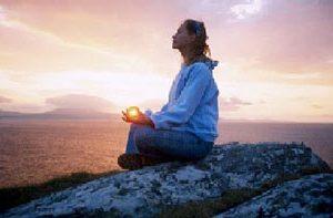 mujer sentada meditando al atardecer